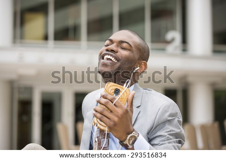 Enjoying the rhythm of his life. Closeup of handsome young man smiling while listening to music - stock photo