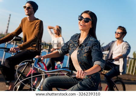 Enjoying the ride. Group of young people riding their bicycles while young beautiful woman looking at camera and smiling - stock photo