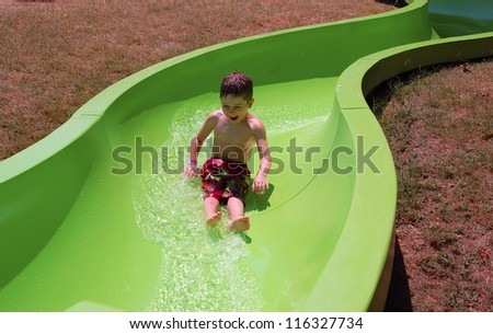 Enjoying the Slide/Young boy enjoys sliding  	down the water slide - stock photo