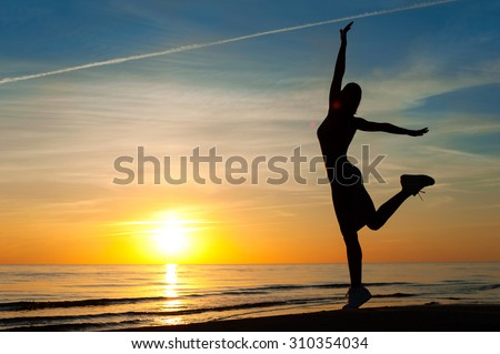 Enjoying the summer evening. Cheerful slender woman silhouette dancing on the sunset with raised up hands on blue sky background on the beach. Summertime multicolored outdoors horizontal image. - stock photo