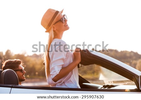Enjoying the sun and fresh air. Side view of cheerful young woman leaning at the wind shield while her boyfriend sitting near on front seat of convertible  - stock photo