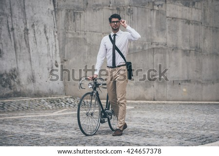 Enjoying the urban lifestyle. Confident young man in glasses looking away and holding hand on his bicycle while walking outdoors - stock photo