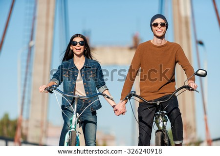 Enjoying their active date. Beautiful young couple riding bicycles along the bridge and smiling - stock photo