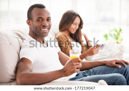 Enjoying their free time together. Handsome young African man sitting on the couch and holding a glass of orange juice while his wife sitting on the background