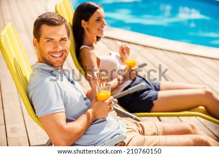 Enjoying their leisure time together. Side view of beautiful young couple sitting at the deck chairs by the pool and drinking cocktails while man looking at camera and smiling - stock photo