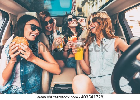 Enjoying their lunch in the car. Four beautiful young cheerful women looking at each other with smile and eating take out food while sitting in car - stock photo