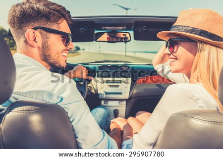 Enjoying their road trip. Side view of cheerful young couple holding hands and looking at each other while sitting inside of their convertible - stock photo