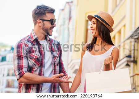 Enjoying their time together. Beautiful young loving couple walking by the street and talking to each other while beautiful woman carrying shopping bags and smiling  - stock photo