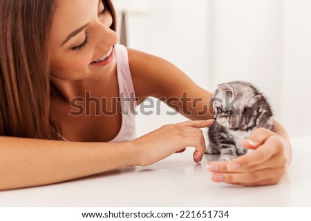 Enjoying their time together. Little cute kitten sitting on the table while being stroked by beautiful young woman