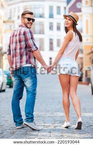 Enjoying their time together. Rear view of beautiful young loving couple walking by the street and looking over shoulder  - stock photo