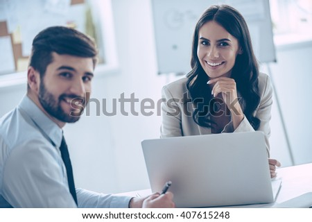 Enjoying their work together. Two cheerful coworkers looking at camera with smile while sitting at the office table  - stock photo