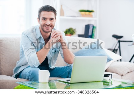 Enjoying time at home. Handsome young man looking at camera and smiling while sitting on the couch at home with laptop laying near him - stock photo
