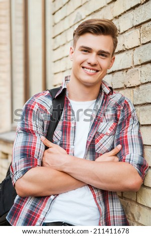 Enjoying time in college. Handsome young man carrying backpack on one shoulder and smiling while leaning at the brick wall  - stock photo