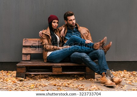 Enjoying time together. Beautiful young couple bonding to each other while sitting on the wooden pallet with grey wall in the background and fallen leaves on the floor - stock photo