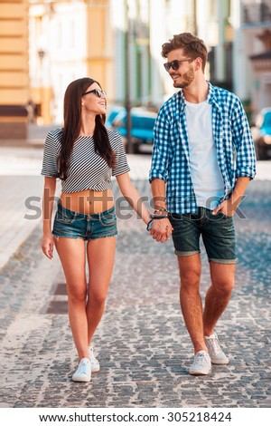 Enjoying time together. Full length of beautiful young loving couple holding hands and smiling while walking along the street together - stock photo
