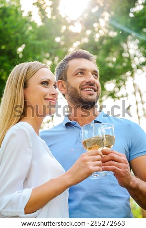 Enjoying time together. Low angle view of happy young loving couple holding glasses with white wine and looking away while standing close to each other outdoors