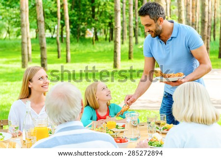 Enjoying time with family. Happy family of five people enjoying meal together while sitting at the dining table in formal garden - stock photo