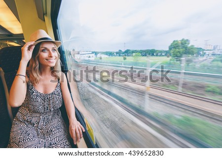 Enjoying travel. Young pretty woman traveling by the train sitting near the window. - stock photo