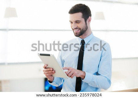 Enjoying work with his new tablet. Handsome young businessman working on digital tablet and smiling while standing indoors - stock photo