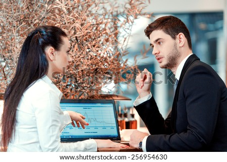 Enjoying working outdoors. Rear view of handsome young man and woman discussing business issues while sitting at the restaurant with laptop - stock photo