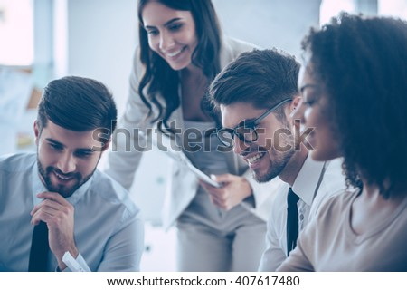 Enjoying working together. Close-up part of group of four people looking down with smile while sitting at office  - stock photo