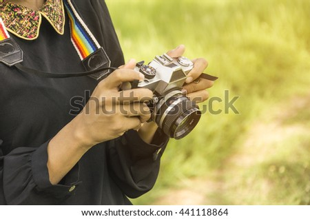 Enjoyment - free happy woman enjoying sunrise. beautiful woman  with old camera on the meadow and sunlight - stock photo