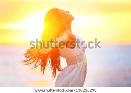 Enjoyment - free happy woman enjoying sunset. Beautiful woman in white dress embracing the golden sunshine glow of sunset with arms outspread and face raised in sky enjoying peace, serenity in nature - stock photo