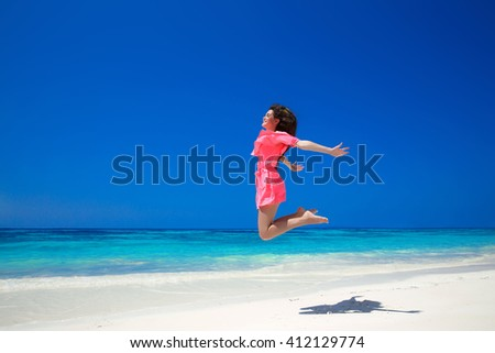 Enjoyment. Happy free woman jumping over sea and blue sky, brunette smiling girl in red dress on tropical beach. Enjoyment. Lifestyle. Freedom. Good life. Travel.  - stock photo