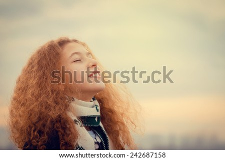 Enjoyment -happy,smiling little girl  enjoying a new breath of fresh air, face raised in sky enjoying peace, serenity in nature.Facial expression,freedom,Relaxation - stock photo