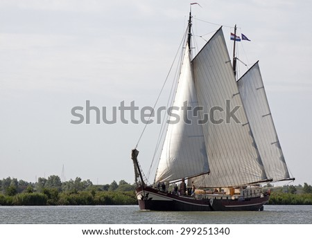 ENKHUIZEN, THE NETHERLANDS - JULY 18,2015: Wooden sailing ship with two masts with sails hoisted illuminated by the sun leave the port with passengers on board on july 18 , 2015 in Enkhuizen, Holland.