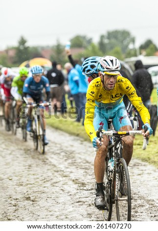 ENNEVELIN, FRANCE - JUL 09:The Italian cyclist Vincenzo Nibali ( Team Astana) wearing the Yellow Jersey on a dirty cobbled road during the stage 5 of Le Tour de France in Ennevelin on July 09 2014.  - stock photo