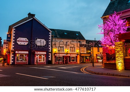 ENNIS, IRELAND - SEPTEMBER 12, 2014: Nightlife at the medieval old part of the popular touristic city in Mid-West Region. It hosts many restaurants and bars, blurry people at the street