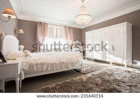 Enormous luxury old fashioned bedroom with crystal chandelier - stock photo