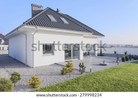 Enormous white modern house with big green garden - stock photo