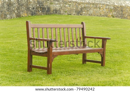 Enpty wooden bench by the garden - stock photo