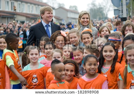 ENSCHEDE, NETHERLANDS - APR 26: Royal Highness Queen Maxima and King Willem Alexander between schoolkids after they just opened the 'koningsspelen' on a school, April 26, 2013 in the Netherlands - stock photo