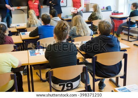 ENSCHEDE, NETHERLANDS - MAR 22, 2016: Kids of 11 years old sitting behind their desks in a school class.