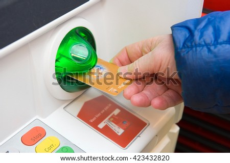 ENSCHEDE, NETHERLANDS - MARCH 31, 2016: A man is entering his bank card into an ATM machine
