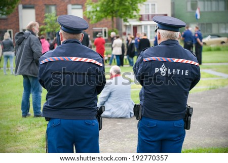 ENSCHEDE, NETHERLANDS - MAY 13: Two policeman are watching the public which is gathering for the remembrance of the firework disaster ceremony which happened in 2000, may 13, 2014 in the Netherlands