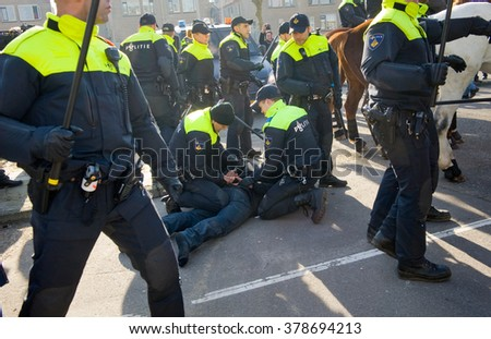 ENSCHEDE, THE NETHERLANDS - FEB 13, 2016: A demonstrator against a huge migrant refugee camp for refugees is being arrested by policemen.