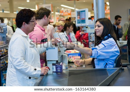 ENSCHEDE, THE NETHERLANDS - JUNE 27: A female cashier of the Albert Heijn supermarket is giving a woman her receipt for the products that she just bought and paid, June 27, 2013 in the Netherlands. - stock photo