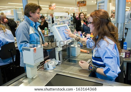 ENSCHEDE, THE NETHERLANDS - JUNE 27: A woman is paying het products that she has bought in the Albert Heijn supermarket at a female cashier, June 27, 2013 in the Netherlands. - stock photo