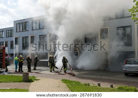 ENSCHEDE, THE NETHERLANDS - 07 MAY, 2015: Firefighters are busy to extinguish a fire in a house - stock photo