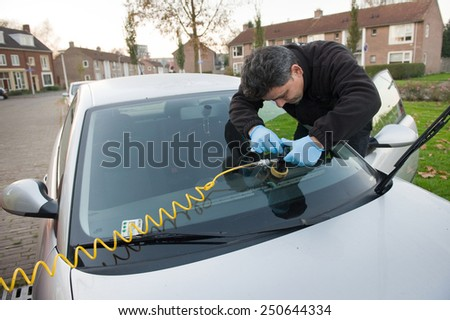 ENSCHEDE, THE NETHERLANDS - 21 NOV, 2014:  A serviceman from 'carglass' is repairing a crack in the windshield of a car on location - stock photo