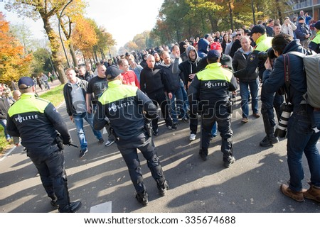 ENSCHEDE, THE NETHERLANDS - OCT 31, 2015: People are demonstrating against a huge migrant refugee camp for syrians close to the part of the city where they live. Police man are stopping them. - stock photo