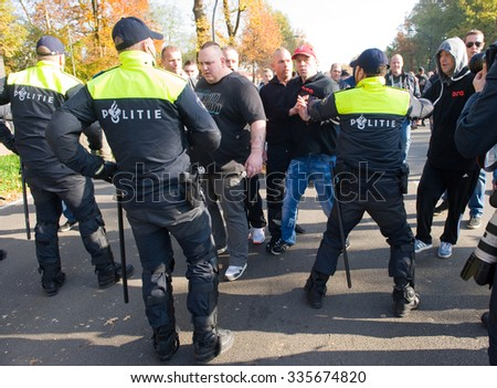 ENSCHEDE, THE NETHERLANDS - OCT 31, 2015: People are demonstrating against a huge migrant refugee camp for syrians close to the part of the city where they live. Police man are stopping them.