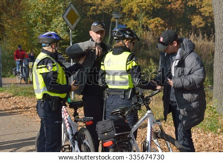 ENSCHEDE, THE NETHERLANDS - OCT 31, 2015: Police women are checking people for ID and weapons before a demonstration against migrant refugees camps for syrians