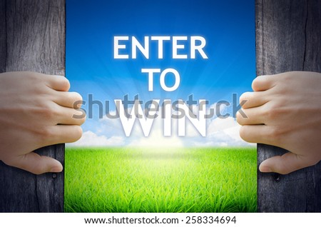 Enter to WIN. Hand opening an old wooden door and found Enter to WIN word floating over green field and bright blue Sky Sunrise. - stock photo
