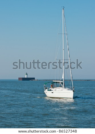 Entering the Cuyahoga River:  A sailboat with sails furled motors south into the mouth of the Cuyahoga River at Cleveland, Ohio with a navigation beacon in the background - stock photo