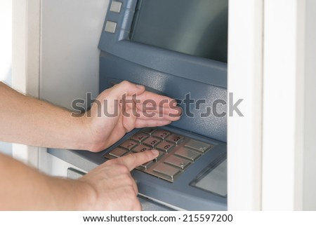 entering the pin code at the atm cash point - stock photo